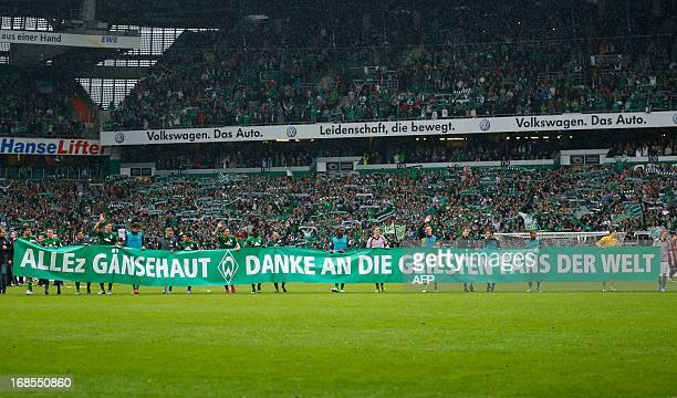 Bremen's players hold a banner reading 'Goose Bumps thanks to the best fans of the world' after the German first division Bundesliga football match...