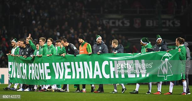 Bremen's players hold up a banner wishing the fans a Happy Christmas after the German first division Bundesliga football match Werder Bremen vs 1 FC...
