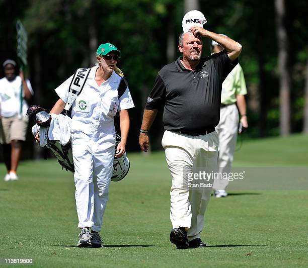 Brenda Calcavecchia walks with her husband Mark Calcavecchia carrying his golf bag during the second round of the Regions Tradition at Shoal Creek on...