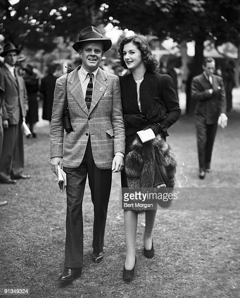 Brenda Frazier of New York City and Buckey Byers of Southampton NY walking outside at the Belmont Race Track on opening day May 13 1940