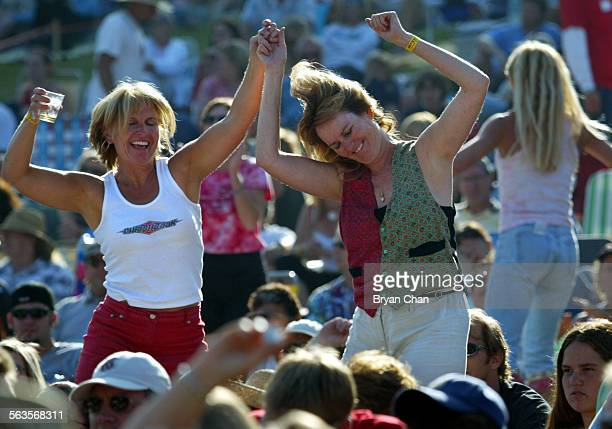 Brenda Montgomery left and Kelley Atwater dance as they listen to Jackson Browne and his band play in the Ventura Hillsides Music Festival Saturday...