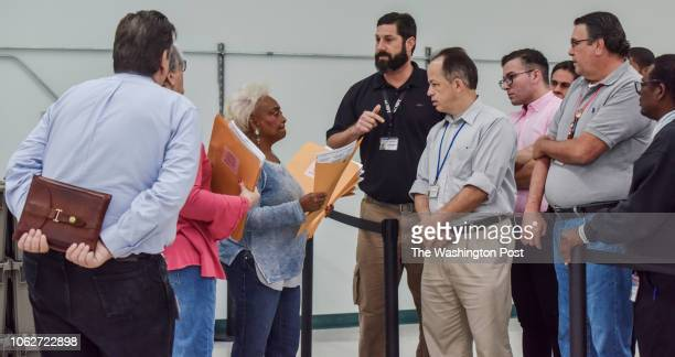 Brenda Snipes, 3rd from L, the Broward County Supervisor of Elections, prepares to have ballots distributed to elections workers and observers who...