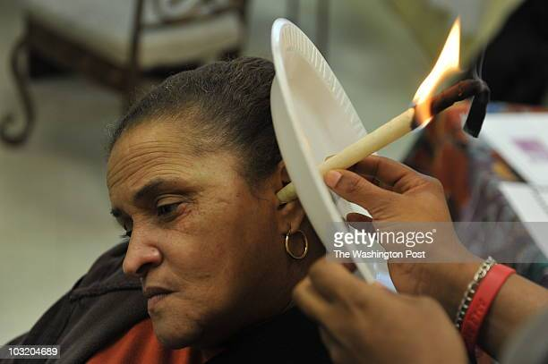 Brenda Thompson gets an alternative medicine treatment called ear candling from Schyla PoyndexterMoore at Secrets of Nature Restaurant and Health...