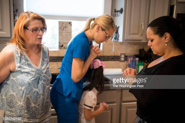 Brenda Woldridge leads a prayer with Heather Rockstroh Holly Cooper and Meredith Cooper after they made a meal for the Holcombe family in San Antonio...