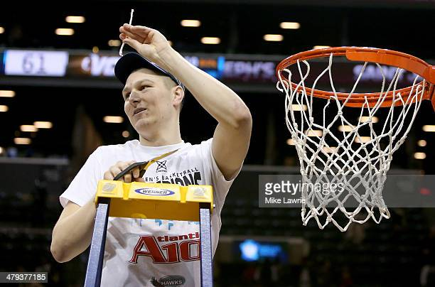 Brendan Casper of the Saint Joseph's Hawks cuts down the net after defeating the Virginia Commonwealth Rams during the Championship game of the 2014...
