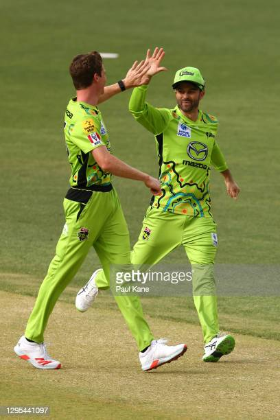 Brendan Doggett and Callum Ferguson of the Thunder celebrate the wicket of Mitch Marsh of the Scorchers during the Big Bash League match between the...