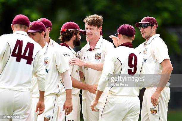 Brendan Doggett of Queensland is congratulated by team mates after bowling out Jackson Bird of Tasmania during day three of the Sheffield Shield...