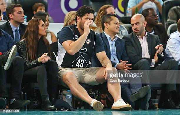 Brendan Fevola drinks a beer as he watches from the crowd with Mia Fevola during the round seven NBL match between Melbourne United and the...
