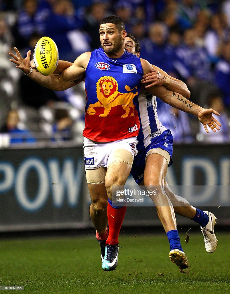 Brendan Fevola of the Lions attempts to gather the ball under pressure from Scott Thompson of the Kangaroos during the round 11 AFL match between the North Melbourne Kangaroos and the Brisbane Lions at Etihad Stadium on June 5, 2010 in Melbourne, Australia.