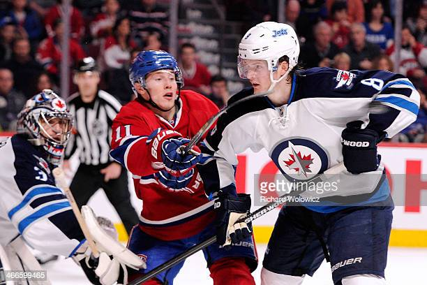 Brendan Gallagher of the Montreal Canadiens attempts to deflect the puck in front of Jacob Trouba and Al Montoya of the Winnipeg Jets during the NHL...