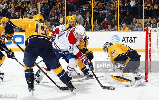 Brendan Gallagher of the Montreal Canadiens battles for a loose puck in front of Pekka Rinne of the Nashville Predators during an NHL game at...