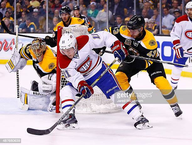 Brendan Gallagher of the Montreal Canadiens carries the puck around thet net in front of Tuukka Rask and Matt Bartkowski of the Boston Bruins in the...