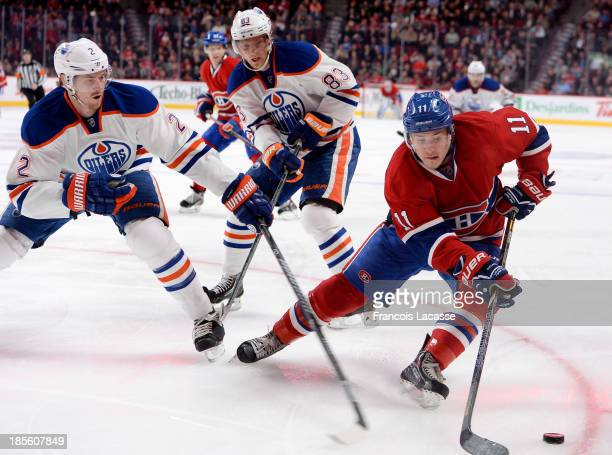Brendan Gallagher of the Montreal Canadiens controls the puck while being challenged by Jeff Petry and Ales Hemsky of the Edmonton Oilers during the...