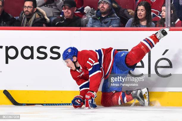 Brendan Gallagher of the Montreal Canadiens falls and hits the boards hard against the Vancouver Canucks during the NHL game at the Bell Centre on...