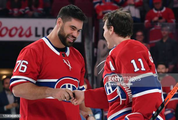 Brendan Gallagher of the Montreal Canadiens greets Canadian football player Laurent DuvernayTardif in a ceremony prior to the NHL game between the...