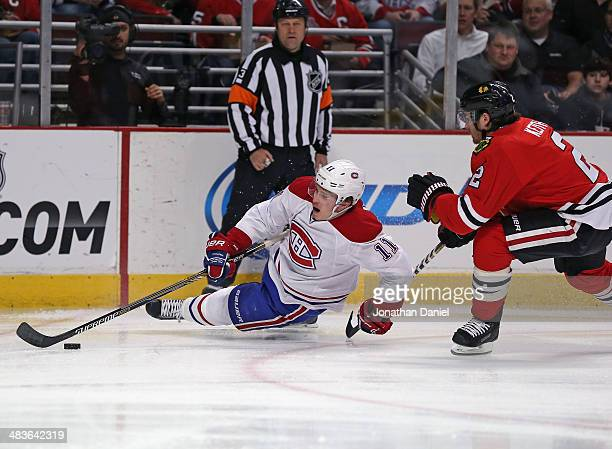 Brendan Gallagher of the Montreal Canadiens hits the ice trying to control the puck under pressure from Duncan Keith of the Chicago Blackhawks at the...