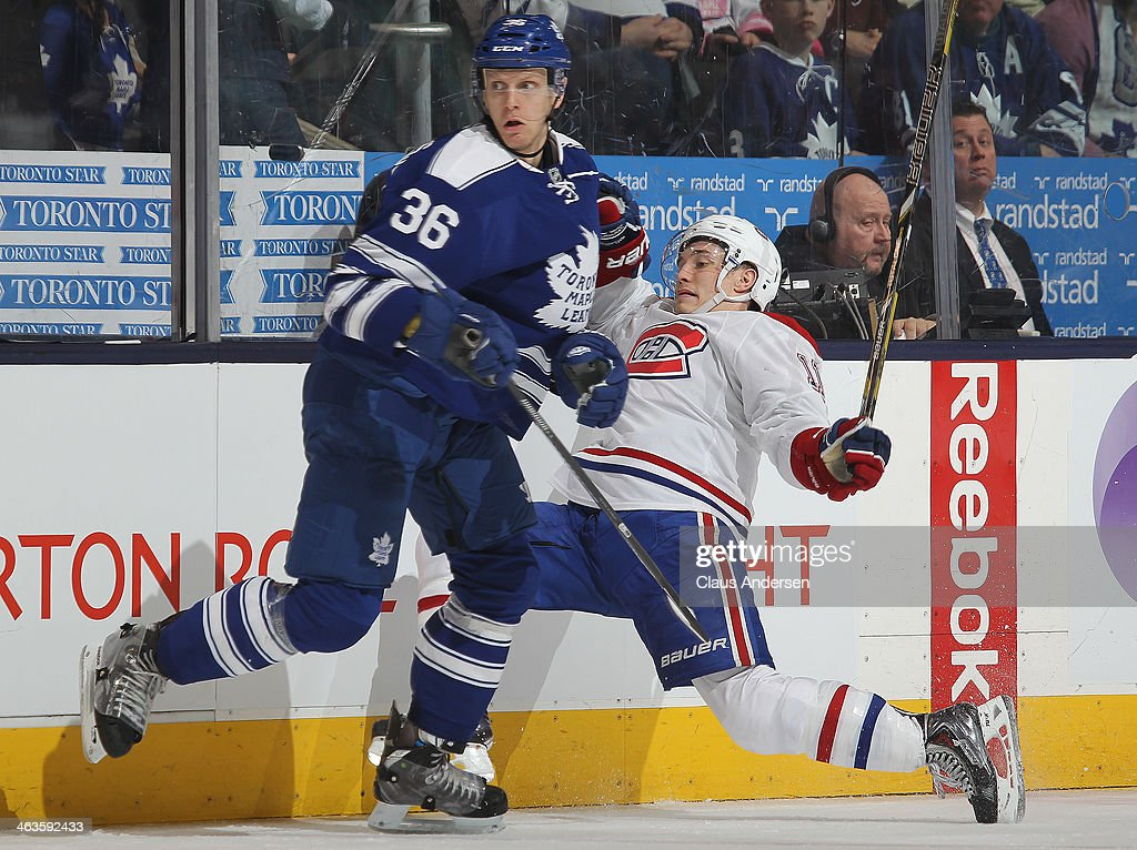 Brendan Gallagher #11 of the Montreal Canadiens is hammered by carl Gunnarsson #36 of the Toronto Maple Leafs during an NHL game at the Air Canada Centre on January 18, 2014 in Toronto, Ontario, Canada. The Leafs defeated the Canadiens 5-3.
