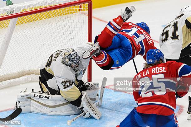 Brendan Gallagher of the Montreal Canadiens jumps over goaltender MarcAndre Fleury of the Pittsburgh Penguins during a NHL preseason game at the...