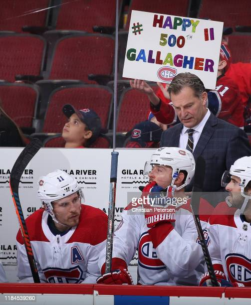 Brendan Gallagher of the Montreal Canadiens sits on the bench as a fan holds a sign congratulating him for playing in his 500th career game during...