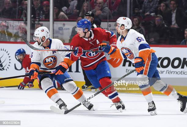 Brendan Gallagher of the Montreal Canadiens skates for the puck against Tanner Fritz and Cal Clutterbuck of the New York Islanders in the NHL game at...