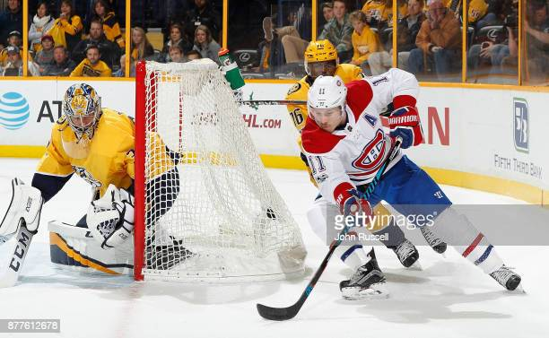 Brendan Gallagher of the Montreal Canadiens skates the puck around the net against PK Subban and Pekka Rinne of the Nashville Predators during an NHL...