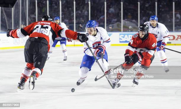 Brendan Gallagher of the Montreal Canadiens skates with the puck against Fredrik Claesson and JeanGabriel Pageau of the Ottawa Senators during the of...