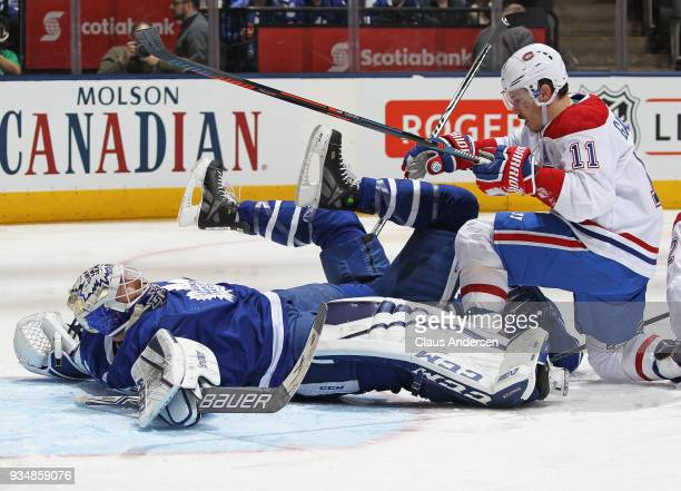 Brendan Gallagher of the Montreal Canadiens slams into Curtis McElhinney of the Toronto Maple Leafs during an NHL game at the Air Canada Centre on...