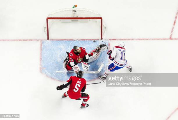 Brendan Gallagher of the Montreal Canadiens squeezes the puck past the outstretched pad of Craig Anderson of the Ottawa Senators as Cody Ceci of the...