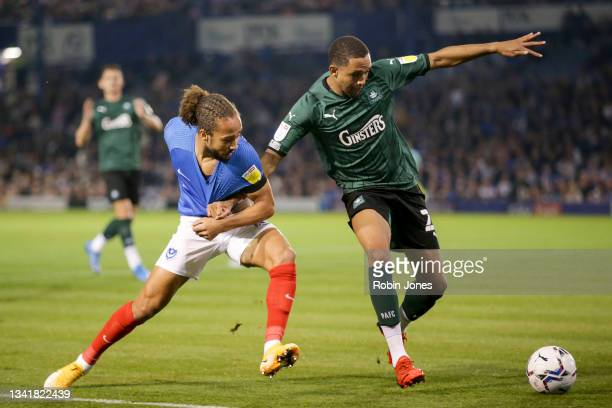 Brendan Galloway of Plymouth Argyle holds off Marcus Harness of Portsmouth FC during the Sky Bet League One match between Portsmouth and Plymouth...
