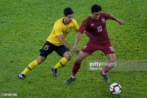 Brendan Gan of Malaysia challenges Teerasil Dangda of Thailand during the 2022 Qatar FIFA World Cup Round Two Asian qualifier between Malaysia and...