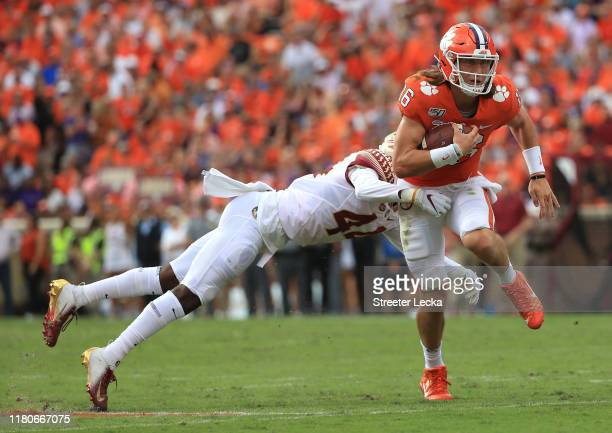 Brendan Gant of the Florida State Seminoles tries to stop Trevor Lawrence of the Clemson Tigers during their game at Memorial Stadium on October 12...