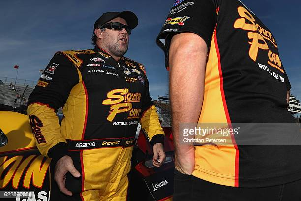 Brendan Gaughan driver of the South Point Chevrolet talks to a crew member on the grid during qualifying for the NASCAR XFINITY Series Ticket Galaxy...