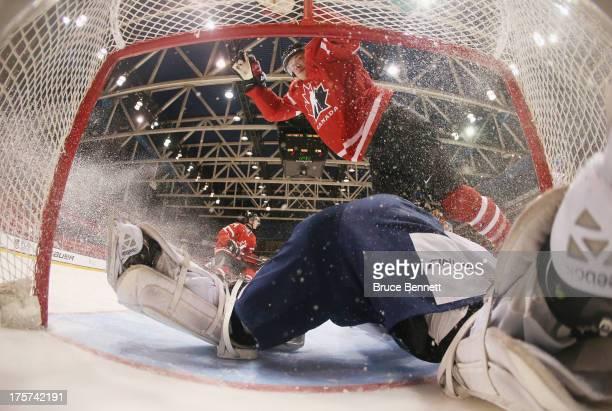 Brendan Gaunce of Team Canada flies over goaltender Joonas Korpisalo of Team Finland during the 2013 USA Hockey Junior Evaluation Camp at the Lake...