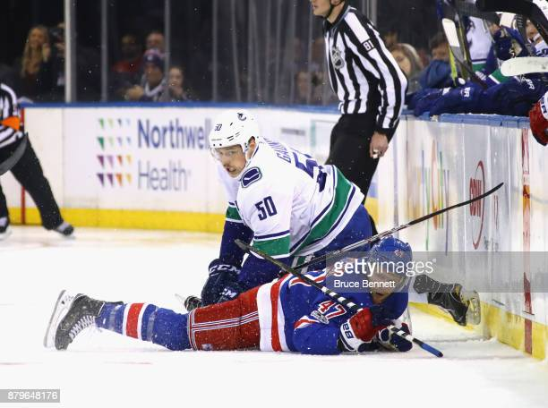 Brendan Gaunce of the Vancouver Canucks and Steven Kampfer of the New York Rangers get tangled up during the first period at Madison Square Garden on...