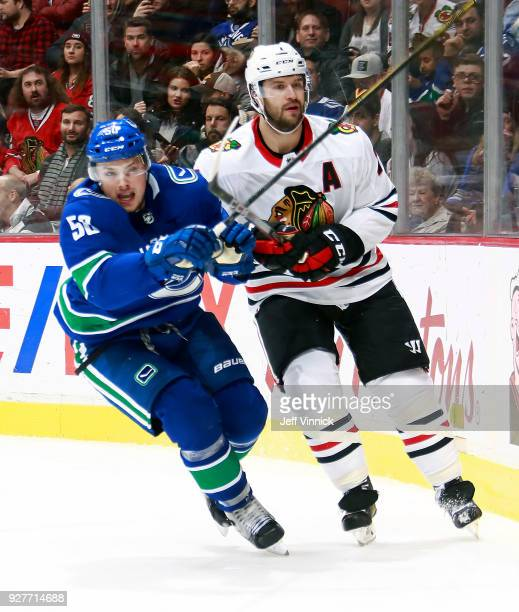 Brendan Gaunce of the Vancouver Canucks checks Brent Seabrook of the Chicago Blackhawks during their NHL game at Rogers Arena December 28 2017 in...