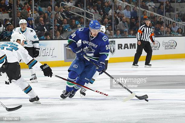 Brendan Gaunce of the Vancouver Canucks handles the puck against Scott Hannan of the San Jose Sharks during a preseason NHL game at SAP Center on...
