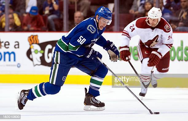 Brendan Gaunce of the Vancouver Canucksskates with the puck while Kyle Chipchura of the Phoenix Coyotes give chase during NHL preseason action on...