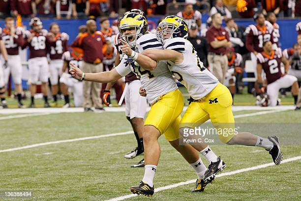 Brendan Gibbons and Drew Dileo of the Michigan Wolverines celebrate after Gibbons kicked a successful 37yard gamewinning field goal in overtime...