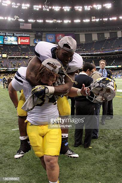 Brendan Gibbons and Fitzgerald Toussaint of the Michigan Wolverines celebrate after Michigan won 2320 in overtime on Gibbons 37yard field goal...