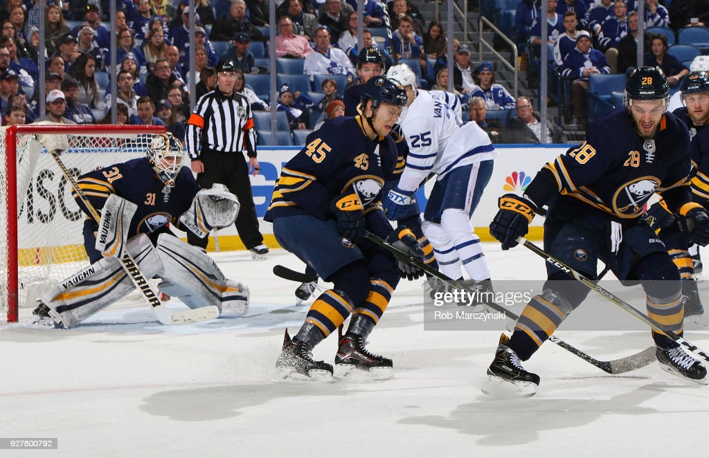 Brendan Guhle #45 and Zemgus Girgensons #28 of the Buffalo Sabres block a shot in front of goaltender Chad Johnson #31during an NHL game against the Toronto Maple Leafs on March 5, 2018 at KeyBank Center in Buffalo, New York. Buffalo won, 5-3.