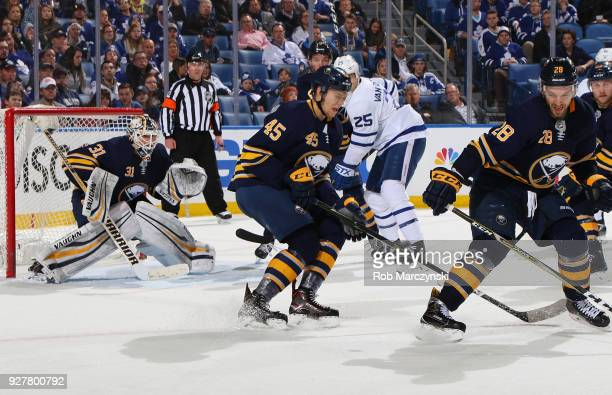 Brendan Guhle and Zemgus Girgensons of the Buffalo Sabres block a shot in front of goaltender Chad Johnson an NHL game against the Toronto Maple...