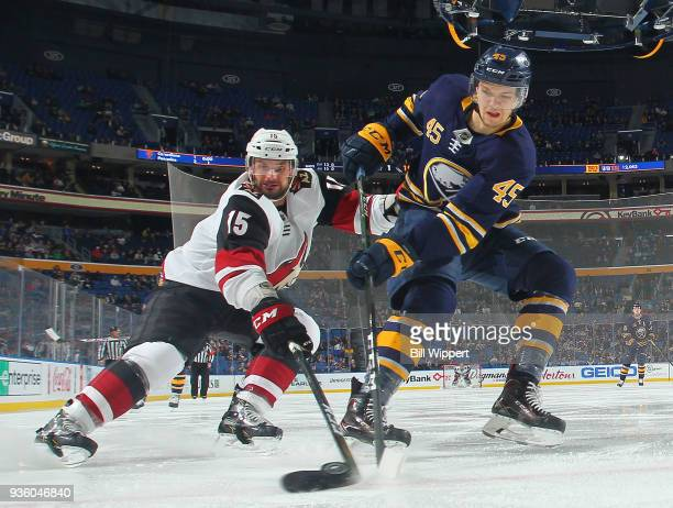 Brendan Guhle of the Buffalo Sabres and Brad Richardson of the Arizona Coyotes battle for the puck along the boards during an NHL game on March 21...