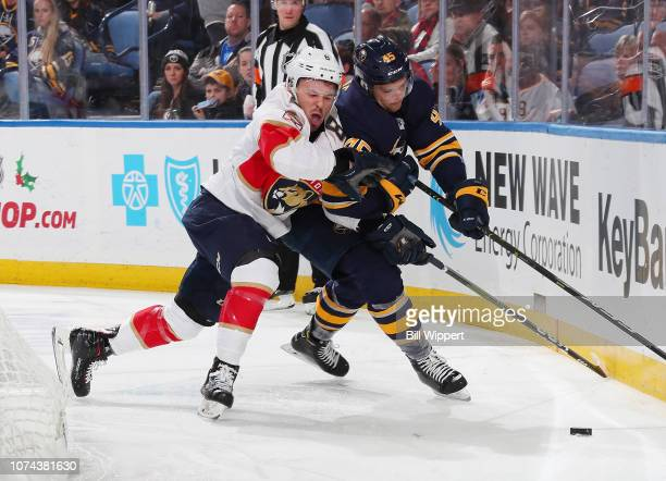 Brendan Guhle of the Buffalo Sabres battles for the puck against Jayce Hawryluk of the Florida Panthers during an NHL game on December 18 2018 at...