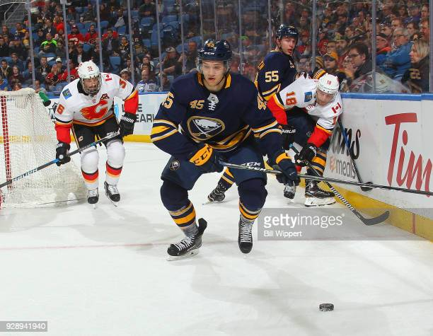 Brendan Guhle of the Buffalo Sabres breaks away with the puck as Troy Brouwer and Matt Stajan of the Calgary Flames give chase during an NHL game on...