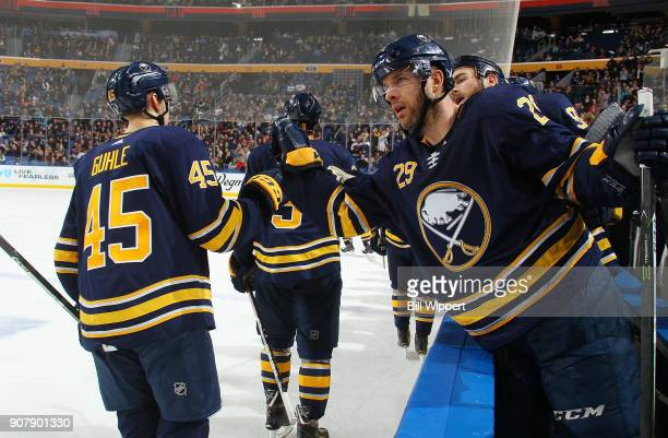 Brendan Guhle of the Buffalo Sabres celebrates his first NHL point with Jason Pominville during an NHL game against the Columbus Blue Jackets on...