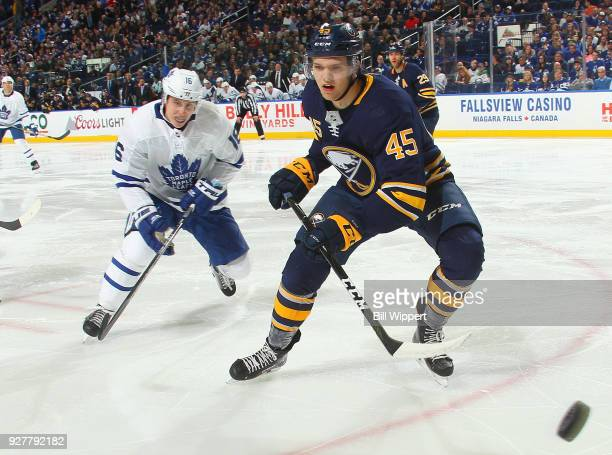 Brendan Guhle of the Buffalo Sabres races for the puck against Mitchell Marner of the Toronto Maple Leafs during an NHL game on March 5 2018 at...