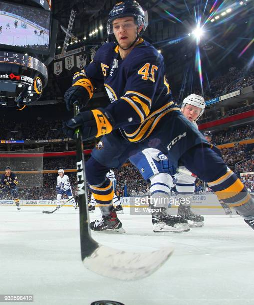 Brendan Guhle of the Buffalo Sabres reaches for the puck during an NHL game against the Toronto Maple Leafs on March 15 2018 at KeyBank Center in...