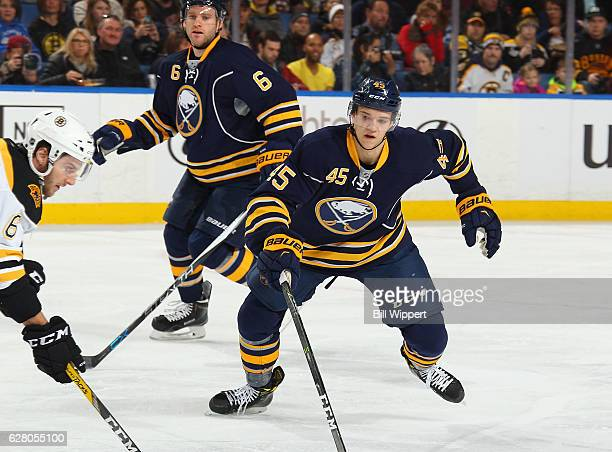 Brendan Guhle of the Buffalo Sabres skates alongside Cody Franson in his first NHL game against the Boston Bruins at the KeyBank Center on December 3...