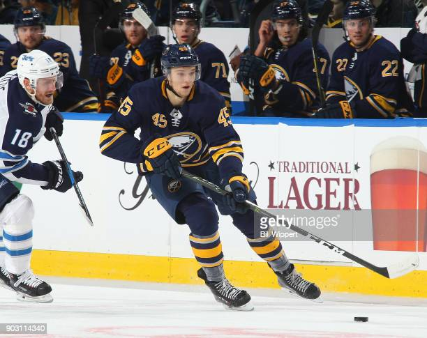 Brendan Guhle of the Buffalo Sabres skates with the puck against Bryan Little of the Winnipeg Jets during an NHL game on January 9 2018 at KeyBank...