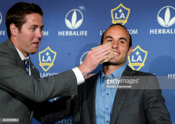 Brendan Hannan wipes lipstick from the right cheek of Landon Donovan of the Los Angeles Galaxy after he announced his retirement following the 2014...